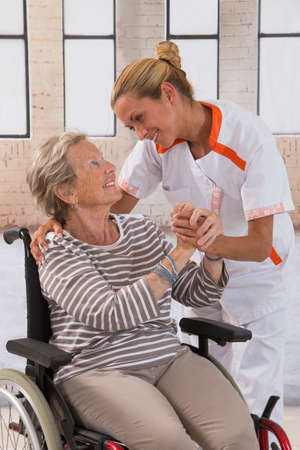 �aucasian: Health care nurse holding elderly ladys hand with caring attitude