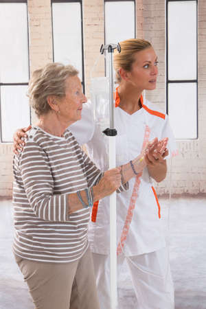 �aucasian: Nurse walking next to a patient with IV drip in hospital