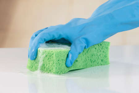 dish washing gloves: Hand in glove blue  with a green sponge