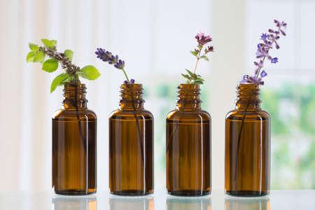 braune Flasche mit aromatischen Kräutern für ätherisches Öl