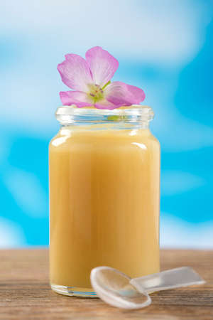 rauwe biologische royal jelly in een kleine fles met bloemen Stockfoto