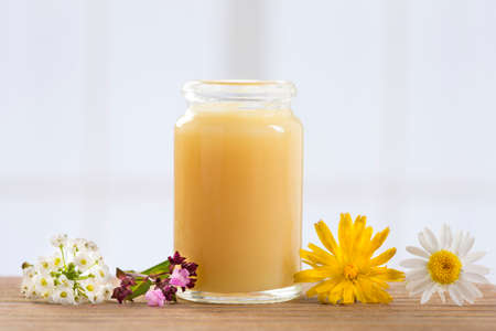 raw organic royal jelly in a small bottle with flowers Stok Fotoğraf