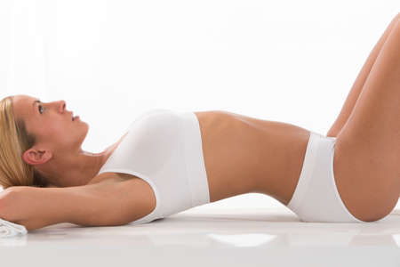 Sexy fit woman with in white underwear lying down.