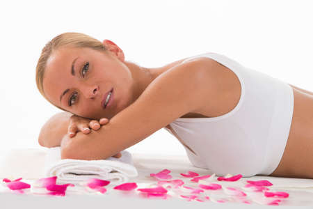 chemical peels: Body care- Young woman resting lying on a towel over white background