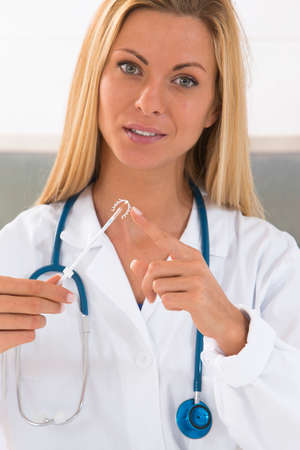 birth control: Yound doctor holding an IUD birth control copper coil device