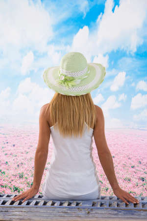 sitted: Lovely  female portrait, sitted with  flower field  background Stock Photo