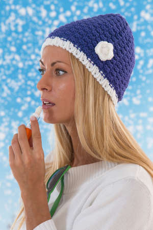 balm: young blond woman applying lip balm on winter background