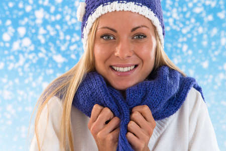 beanies: Woman with blue scarf and blue hat on snowing background Stock Photo
