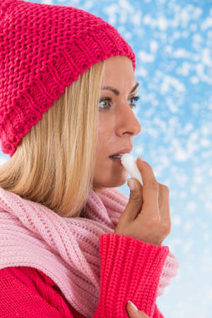 balm: young  woman applying lip balm on snowing  background