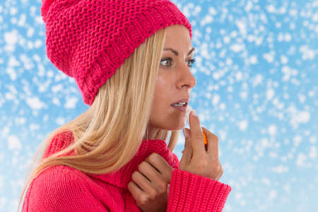 young  woman applying lip balm on snowing  background
