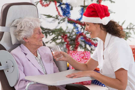 bring: caring  caregiver bring a glass of water to senior woman