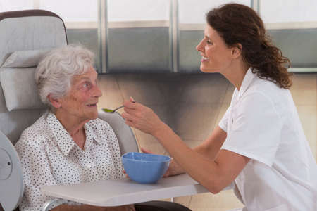 oude vrouw in een rolstoel wordt gevoed in een bejaardentehuis setting. Stockfoto