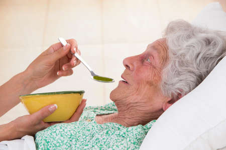 Nurse giving soup to sick elderly woman at home in bed