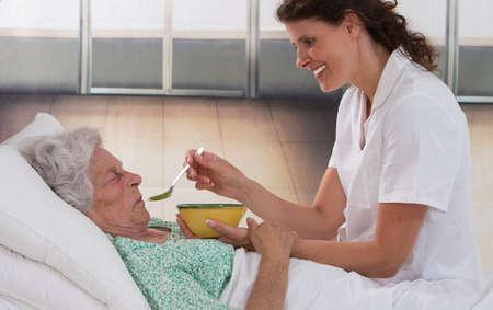 persona de la tercera edad: Enfermera que da sopa a anciana enferma en casa en la cama