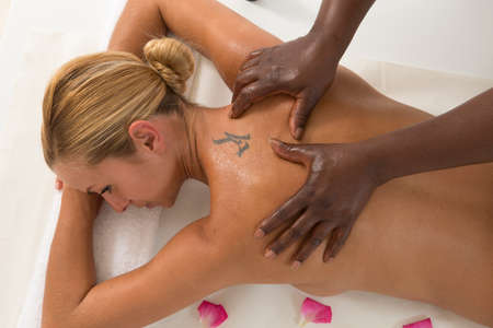woman back of head: An attractive caucasian woman lying down on a massage bed at a spa Stock Photo