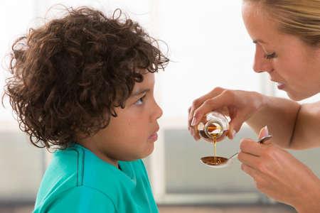 jarabe: Poco jarabe de la medicina niño de beber líquido de alimentación madre mano Foto de archivo