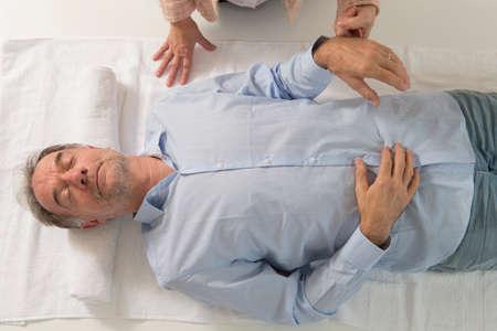 Hogere mens wordt gehypnotiseerd door hypnotherapeut