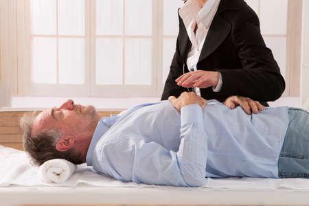 Senior man being hypnotized by hypnotherapist