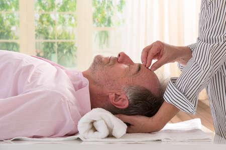 催眠療法によって催眠術をかけている年配の男性