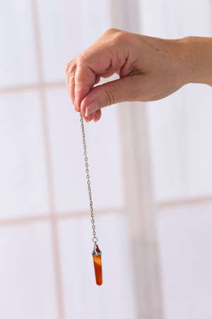 dowsing: Hand with pendulum tool for dowsing.