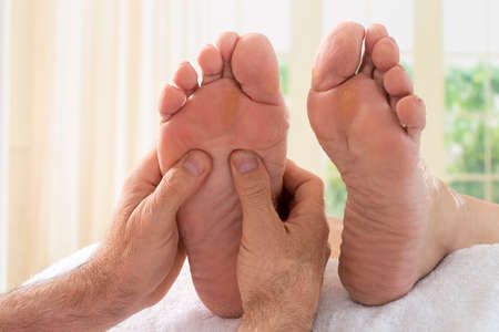 bare foot: Therapist hands giving massage to soft bare foot