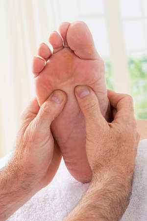 reflexology: Therapist hands giving massage to soft bare foot