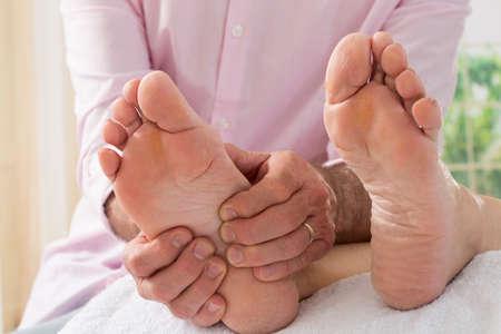 reflexologie: mains thérapeute donnant massage aux pieds nus doux Banque d'images