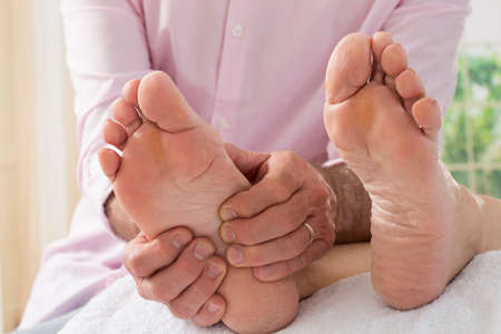 human blood circulation: Therapist hands giving massage to soft bare foot