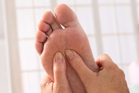 reflexologie plantaire: Therapist hands giving massage to soft bare foot