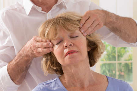 cranial: cranial osteopathy therapy doctor hands in woman hea Stock Photo