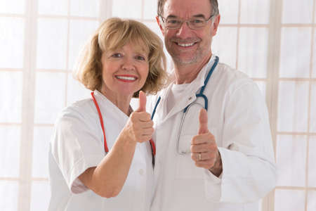 mature woman: Medical team senior male doctor with professional female colleague portrait