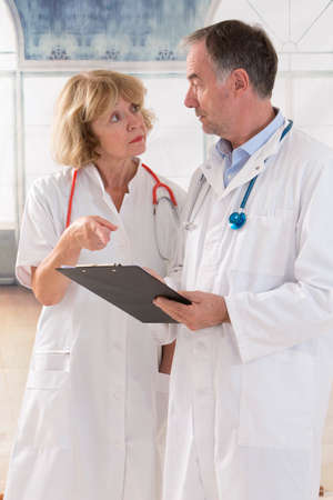prescribing: Two doctor team reading on clipboard