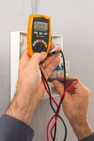 multimeter: Hand of an electrician with multimeter probe at an electrical switchgear