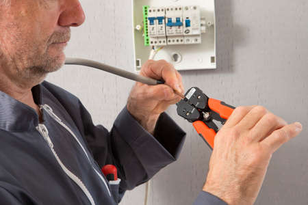 hands off: Electrician peeling off insulation from wires - closeup on hands and pliers Stock Photo