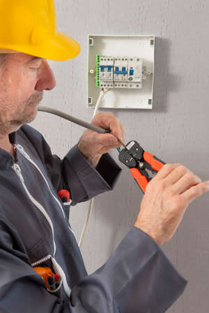 electricista: Electricista despegando de aislamiento de los cables - de cerca en las manos y alicates