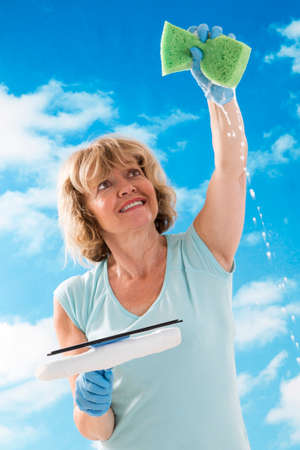 houseclean: Woman  with sponge and squeegee cleaning the misted window