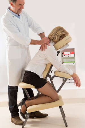 Woman having back massage in medical or business office Stock Photo