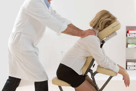 pressure massage: Woman having back massage in medical or business office Stock Photo