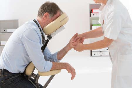 Woman having back massage in medical or business office Standard-Bild