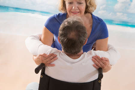 taking a wife: loving wife taking her disabled husband for a walk on seaside