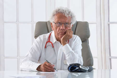 physician: Portrait of an overworked doctor rubbing his head, looking totally stressed out