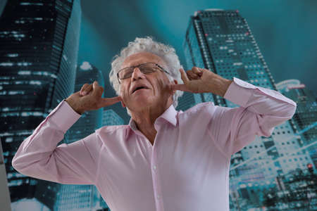 noises: senior business man hahing troubles with city noises Stock Photo
