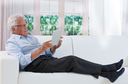 handsome old man: Portrait of senior man relaxing in sofa at home with a magazine