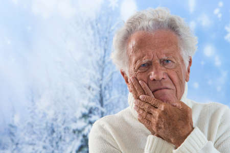 ache: unhappy senior man with painful toothache, isolated on winter snowing background.