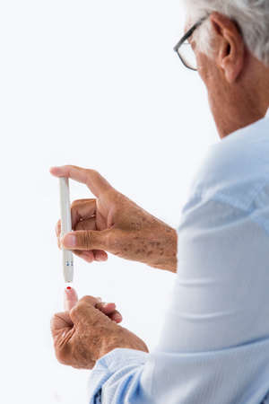 third age: Senior man doing blood sugar test at home Stock Photo