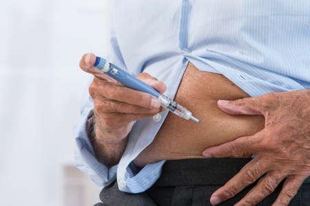 inyeccion: Hombre de inyección de insulina madura en el abdomen