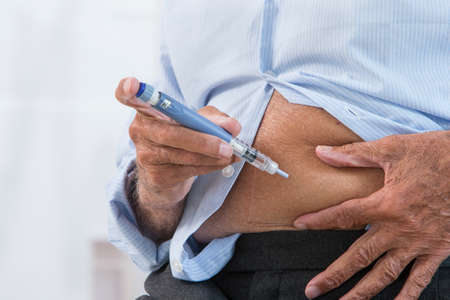 hormone  male: Mature man injecting insulin in his abdomen