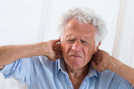 senior pain: Senior man suffering from neck ache Stock Photo