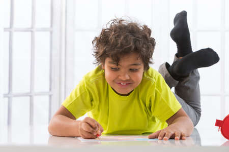 niños riendose: Portrait of kid drawing on floor in living-room
