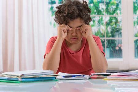 deberes: Cansado del adolescente que hace la preparaci�n en el Home